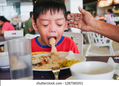 Boy puking on plate after eating lunch meal in food court with helping hand