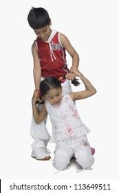 Boy pulling hair of his sister