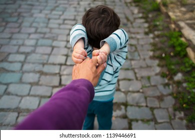 The boy is pulling his father's hand. Dad walks with his son along the city street. The child is capricious and does not let go of the parent's hand.