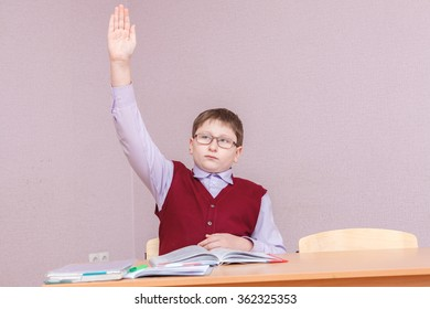 boy pulls a hand up sitting at his desk
