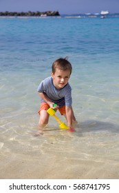 Boy pumps sea water with water gun on the beautiful beach during a summer day