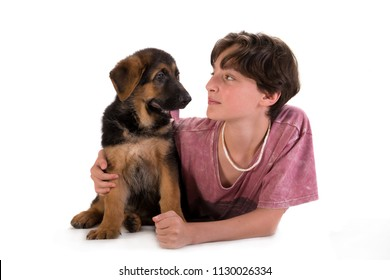 Boy and puppy portrait in studio, 11 years old boy hugs German shepherd pup isolated on white background. Looking at each other.