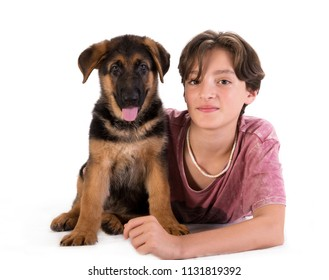 Boy and puppy portrait in studio, 11 years old boy hugs German shepherd pup isolated on white background. Looking at the camera.