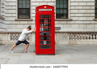 Boy pushes a red telephone box in London. Front view