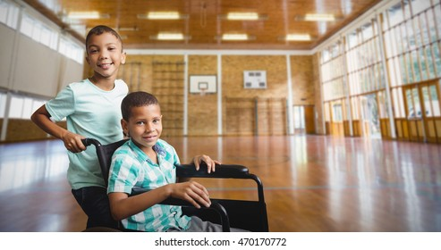 Boy pushing friend wheelchair against image of a sports hall