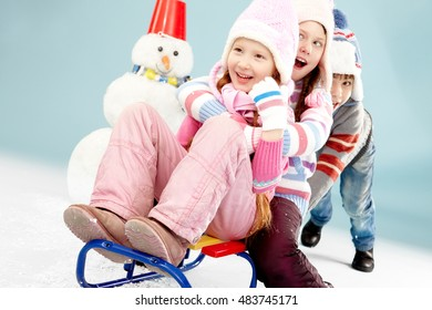 Boy pushing sled with two little girls sitting on it