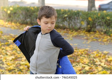Boy puts on a blue jacket walking in the autumn park, because it's cold outside