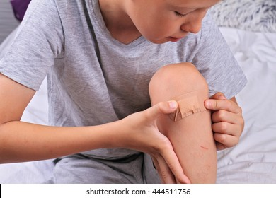 Boy Putting Band-Aid On His Knee. Boy with a plaster on his injured knee. Encouraging Autonomy in children, Hygiene concept.