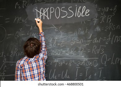 boy putting a cross over impossible on blackboard