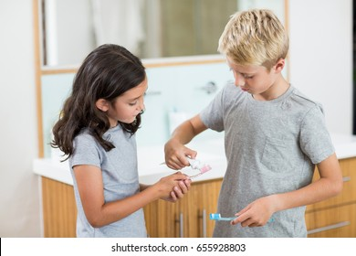 Boy putting toothpaste on sister toothbrush in bathroom at home