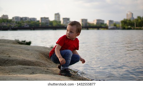 Boy quatting by the still pond in red T-shirt and looking back