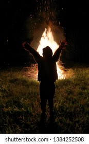 The boy raised his hands to the fire