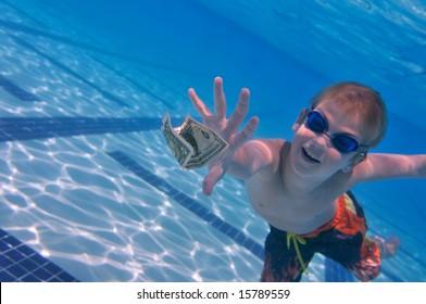 Boy reaching dollar bill, swimming pool underwater shot