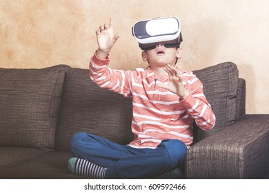 Boy reacts while experiencing virtual reality at home