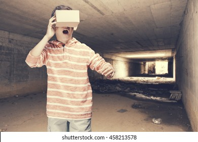 Boy reacts while wearing virtual reality headset. Conceptual cross processed image with shallow depth of field