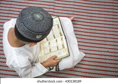 Boy reading al Quran during fasting month (Ramadhan ).  DOF and copy space.
