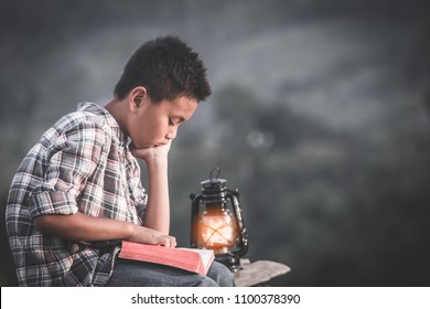 Boy reading bible with light of oil lamp, christian concept.