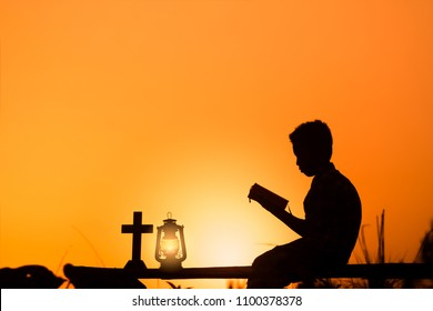 boy reading bible on wood , christian silhouette concept.