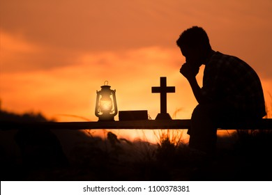 boy reading bible and praying on wood , christian silhouette concept.