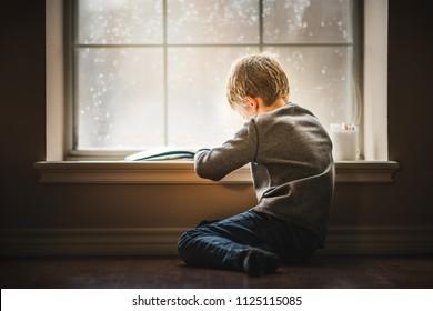 Boy reading book by window