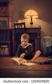Boy is reading a book on the floor. Vintage image with selective focus and toning