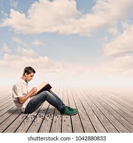 boy reading a book on a wharf