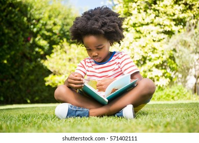 Boy reading a book in a park on a sunny day