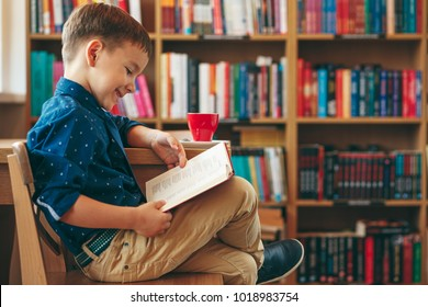 Boy reading a book sitting on a chair near a table with a cup of tea on the background of multi colored bookshelf in the library . Education, Knowledge, getting ready for school.
