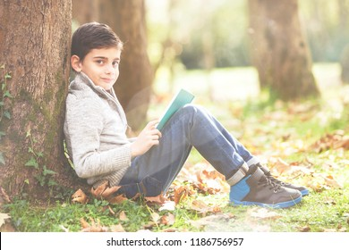 Boy reading his book under a tree in a autumn background. (Soft focus image, retro toned  for vintage effect)