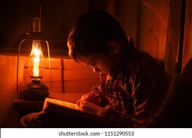boy reading in the light of an old lamp. the child sitting on a dark staircase with a book
