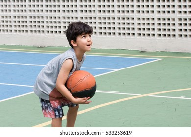 Boy ready to throw basket ball on court