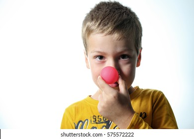 Boy with red ball nose in his left hand with white background