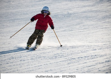 The boy in a red jacket on skis in mountains