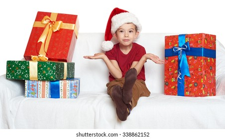 boy in red santa helper hat with gift boxes make a wish - christmas holiday concept