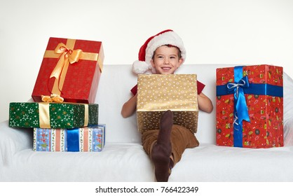 Boy in red santa helper hat with gift boxes sit on sofa. White background. Christmas holiday concept