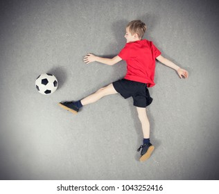 boy in red shirt from above playing soccer ball