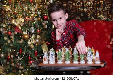 A boy in a red shirt playing chess, emotions on his face. Next is a Christmas tree. The concept of the celebration of New year or Christmas