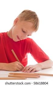 boy in a red shirt sitting draws