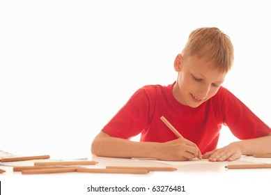 boy in a red shirt sitting and draws