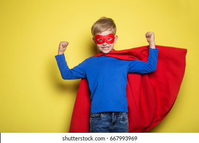 Boy in red super hero cape and mask. Studio portrait over yellow background