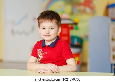 boy in a red t-shirt sits at a Desk in a kindergarten . Portrait of a three-year-old boy in kindergarten