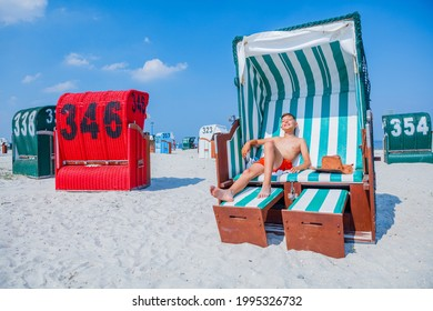 Boy relax on the beach korbs on Nord sea in germany