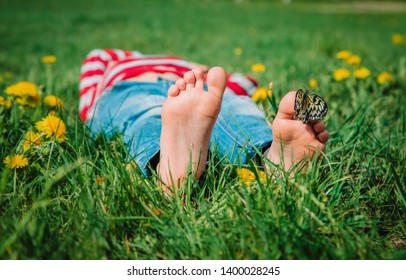 boy relaxed on green grass, butterfly sitting on his feet in nature
