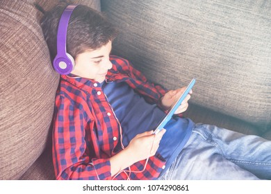 Boy relaxing at home listening to his favorite music using his tablet and a set of headphones
