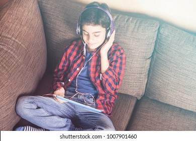 Boy relaxing listening to his favorite music using his tablet and a set of headphones