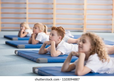Boy relaxing on a blue mat with friends in a primary school
