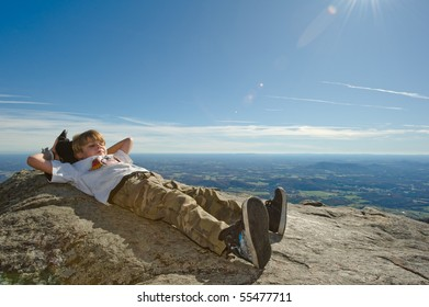 Boy Relaxing on Cliff
