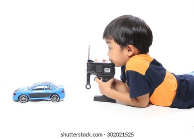 Boy with remote control makes toy car isolated on white