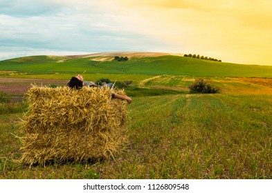 Boy resting or sleeping on bale of hay. Man looking at the landscape of a rural meadow during a sunset. Concept of calm, solitude, peace or resting.