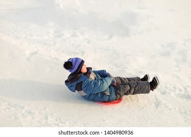Boy rides on an ice-boat from a snow slide. Sledding snow saucer - winter children's fun.